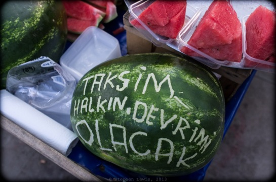 "Revolutionary melon slices for a revolutionary market. The slogan scratched onto the watermelon: ""Taksim, the people's revolution is coming."" But, no matter how progressive, red, and tasty such melon slices may have been, the going price -- five lira per serving -- was counter-revolutionary at best! (Fuji X100) (Click on image to enlarge)."