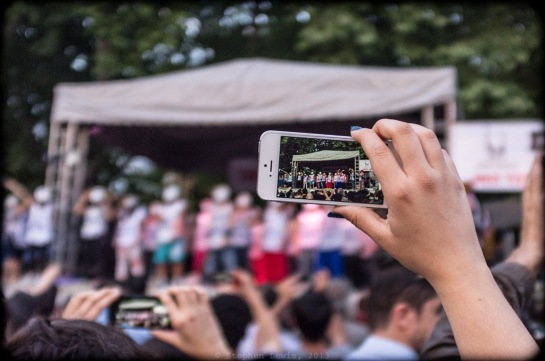 """iPhone as surrogate telephoto lens. In focus on the iPhone screen and out of focus in the background: """"guerilla theater"""" performed by a troupe of striking Turkish Airlines workers, Gezi Park, first week of occupation. (FujiX100)"""