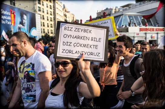 "The Turkish Prime Minister announced that he would never kneel before ""looters/freebooters"" occupying Gezi Park and the marchers demonstrating on their behalf.  This marching folklorist carries a sign liberally translated as: ""Even when we dance Zeybek (a traditional dance involving crouching steps), we do not kneel!"""