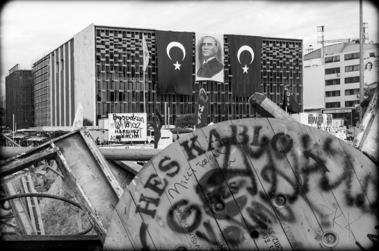 Atatürk Curlutral Center, the morning after a brutal siege by police a week and a half ago.  Immediately after the siege, the police removed banners hung by left-wing groups and replaced them with a portrait of Atatürk flanked by two Turkish flags.  In an uncharacteristic departure from the usual iconography of of the present regime, a portrait of Prime Minister Erdoğan is conspicuous in its absence. (Fuji X100).  (To magnify image, click on photo)