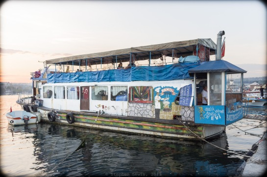 An anchored boat converted to a fish sandwich and fried anchovy restaurant, Golden Horn, Hasköy, Istanbul, 2013.  Note the kitchen topped with jaunty chimney  perched precariously in the after-fitted poop-deck. (Fuji X100)  Click to enlarge.