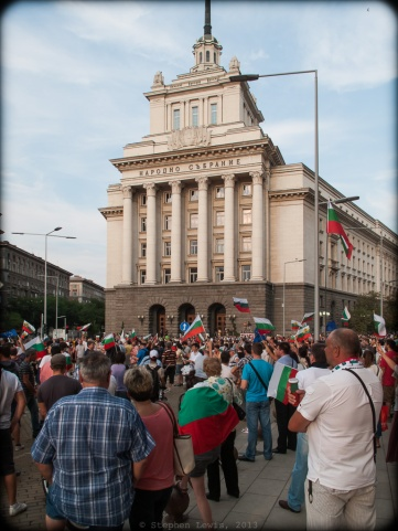 "Sofia, Bulgaria.  Demonstrators gathering on a recent weekday evening in front of the National Assembly Building, a ""Stalinist Wedding Cake"" style edifice that during the years of the Soviet Bloc housed the headquarters of the Bulgarian Communist Party.  Out of frame to the left: The offices the Bulgarian Council of Ministers.  Out of frame to the right: The offices of the President of the Republic of Bulgaria. The National Assembly Building, by the way, stands at the very epicenter of Sofia, at the convergence of three ages-old roadways around which the city rose, at the remains of the east gate of the Roman city of Serdica, and at the foot of a rise upon which, during Ottoman times, stood the clock tower that regulated the city's pace.  (Canon G10) (Click to enlarge.)"