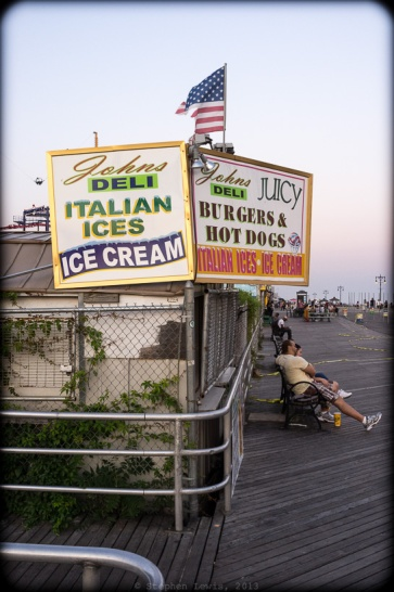 "America's shoreline: John""s Italian Ices and a tattered US flag. Sunset at the Coney Island Boardwalk, 2011. (Fuji X100)"