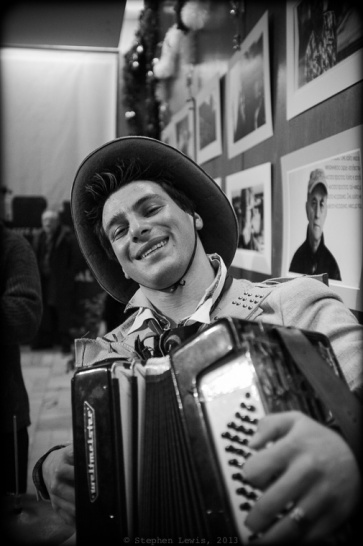 "Music at the premiere was provided by a high-spirited, virtuoso Roma (Gypsy) accordionist, with the very non-Bulgarian, non-Roma name of ""Jimmy.""  Jimmy reinforces his seemingly American moniker with a seemingly American cowboy hate.  Johnny invited Jimmy to the premiere after hearing him play on the street nearby.  It was Jimmy's fault that I danced rather than photographed! (Fuji X100, specs as per above). Click on image to enlarge."