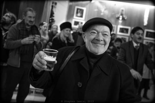 "Legendary guitar Virtuoso and life-long ""Filibeli"" (see body text for definition), Ognian Videv, wearing an English-style Kangol and holding, in lieu of his signature guitar, a signature glass of bear, December, 2013.  (Fuji X100, specs as per above.) Click on photo to enlarge."