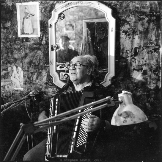 "The late Dimo Kolarov playing accordion for the last time, Sofia, Bulgaria, 1996. Reflected in the mirror, Georgi ""Johnny"" Penkov. Rolleiflex Tessar f3.5, 400ASA b/w negative film pushed to 800ASA, scan of print. Click to enlarge"