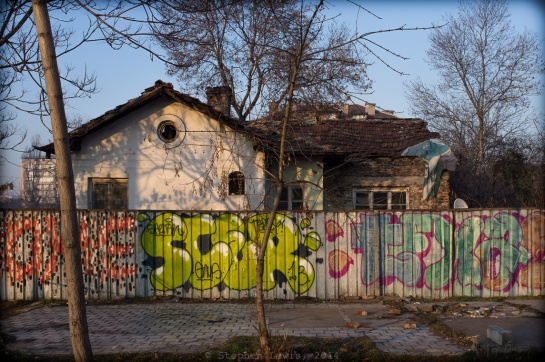 A Long-Vanished Nightspot: A patch of pavement, a corrugated metal fence, and a rundown cottage on a main thoroughfare in Sofia, Bulgaria –  the likely location of a nightclub once owned and run by  Keva, a legendary Romani (Gypsy) vocalist in the years preceding the Second World War.  In its day, Cafe Keva was a popular gathering-place for Sofia residents of diverse ethnicities and walks of life.  Fuji X100, 2014. Click on image to enlarge.