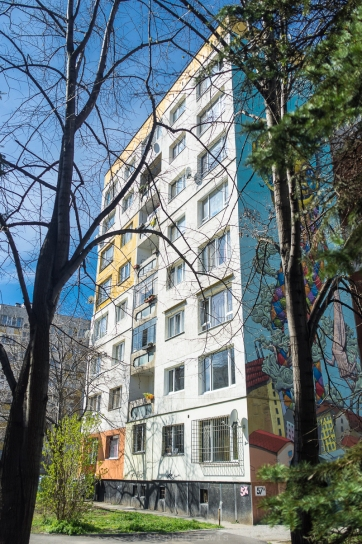 Poduyane quarter, Sofia, Bulgaria, 2016. Fuji X100 w/ +1.4 lens adaptor. The uncoordinated color schemes of privately insulated apartments on the facade lends an accidental Mondriaan-like counterpoint to the neo-psychedelica of the mural on the lateral face of the building.